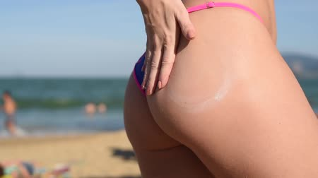 солнечные ванны : A woman in a seductive mini bikini puts sunscreen on the buttocks. A girl with a beautiful figure rubs suntan lotion on the beach. Female hand spreading protective cream. Close up video.