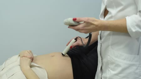 ultrasound scan : A gynecologist examines a pregnant woman. Fetal doppler heart auscultation. Patient at doctor office. Assessment of heartbeat and control of all fetal cardiac activity. Concern about the health.