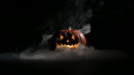 uğursuz : Halloween, orange pumpkin with a scary luminous face on a dark background. Gray thick smoke comes out.