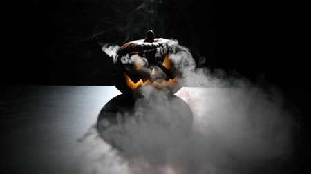korkunç : Halloween, orange pumpkin with a scary luminous face on a dark background. Gray thick smoke comes out.