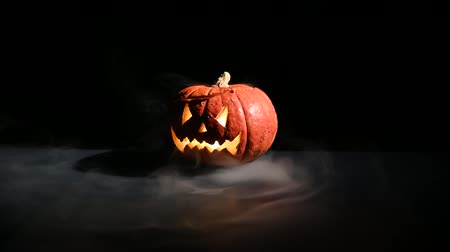 tykev : Halloween, orange pumpkin with a scary luminous face on a dark background. Thick gray smoke comes out and spreads across the black table. A close-up of a flashlight on the eve of all the saints