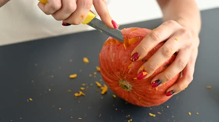 yüz buruşturma : A woman carves an evil grimace on a pumpkin for Halloween with a paper knife. Close up of female hands making jack-o-lantern on a black table on the eve of all saints.