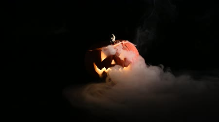 grumpy : Halloween, orange pumpkin with a scary luminous face on a dark background. Thick gray smoke comes out and spreads across the black table. A close-up of a flashlight on the eve of all the saints