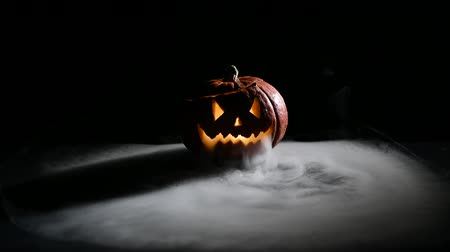 スプレッド : Halloween, orange pumpkin with a scary luminous face on a dark background. Thick gray smoke comes out and spreads across the black table. A close-up of a flashlight on the eve of all the saints