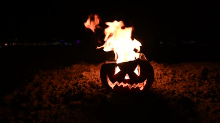 резной : Scary Halloween pumpkin is spewing fire flame on black Background. Jack lantern burns from the inside with an open lid on the ground.
