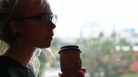 урод : An unusual girl with dreadlocks on her head and tunnels in her ears drinks coffee and eats a donut in a cafe. A young woman in glasses is having breakfast while sitting by the window during the rain.