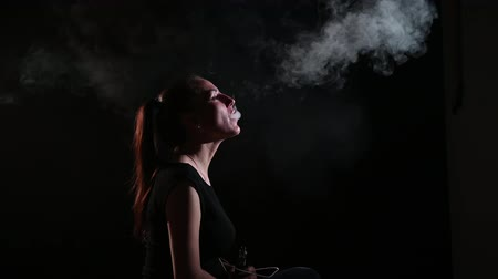 bad habits : The brunette smokes an electronic cigarette on a black background, releases thick smoke from her mouth. Portrait of a woman smoking a vape, hovering. Stock Footage