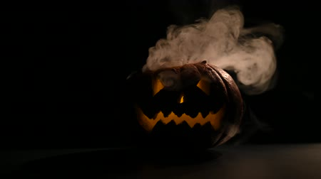 grumpy : Halloween, orange pumpkin with a scary glowing face in the dark. Thick gray smoke comes out and spreads on the black table. A close-up of a flickering flashlight on the eve of all the saints.