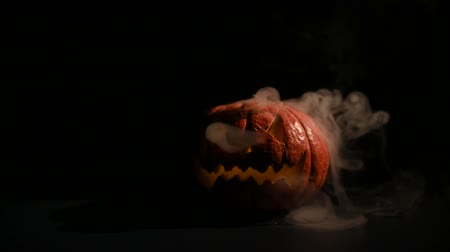 grão : Halloween, orange pumpkin with a scary glowing face in the dark. Thick gray smoke comes out and spreads on the black table. A close-up of a flickering flashlight on the eve of all the saints.