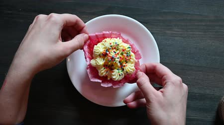 słodycze : Woman eating a sweet cupcake with cream and confiti in a cafe. Large female hands unfolding cupcake. Top view of a white plate with cake.