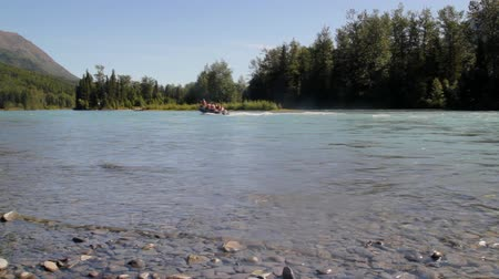 zodiak : Motor boat (zodiak type) going past on the Kenai River near Cooper Landing, Alaska in summer with waves on a rocky beach and blue skies.
