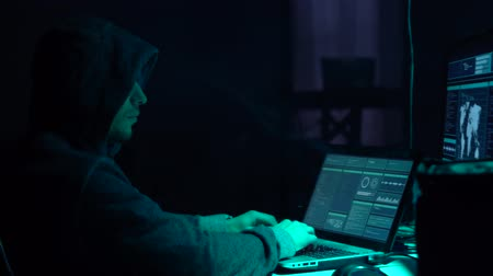 maska : Wanted hackers coding virus ransomware using laptops and computers in the basement. Cyber attack and system breaking concept. Wideo