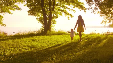 pole : Happy family walking near the sea. Field and trees in countryside. Warm colors of sunset or sunrise. Loving mother and beautiful daughter. Love and parenthood.