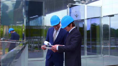 retailing : Real estate developers in helmets. New office construction. Confident business men and architect talking in front of modern office building. Businessman and his colleague.