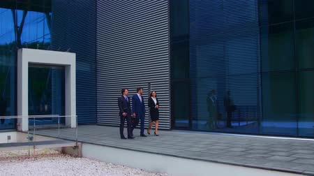 ホワイトカラー : Confident businesspersons talking in front of modern office building. Businessmen and businesswoman have business conversation. Banking, professional job and financial market.