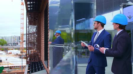 воротник : Real estate developers in helmets. New office construction. Confident business men and architect talking in front of modern office building. Businessman and his colleague.