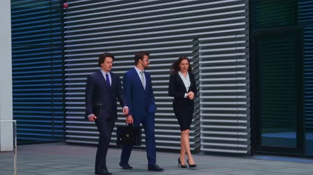 bankier : Confident businesspersons talking in front of modern office building. Businessmen and businesswoman have business conversation. Banking, professional job and financial market.