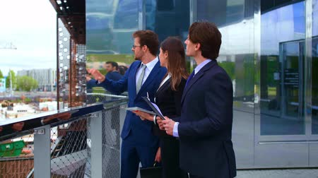 воротник : Confident businesspersons talking in front of modern office building. Businessmen and businesswoman have business conversation. Banking, professional job and financial market.