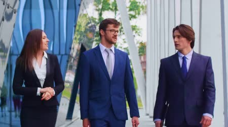 банкир : Confident businesspersons talking in front of modern office building. Businessmen and businesswoman have business conversation. Banking, professional job and financial market.