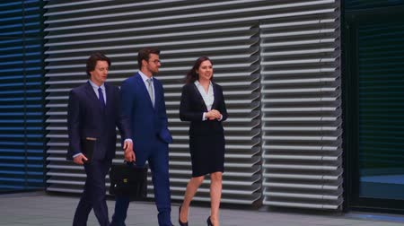 tezgâhtar : Confident businesspersons talking in front of modern office building. Businessmen and businesswoman have business conversation. Banking, professional job and financial market.