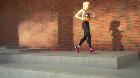 drabina : Young, attractive and sporty blond girl jogging outdoor in the streets. Healthcare, sport, fitness and lifestyle.