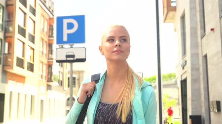 delgado : Young, attractive and sporty blond girl walking outdoor with a sport bag. Healthcare, fitness and lifestyle.