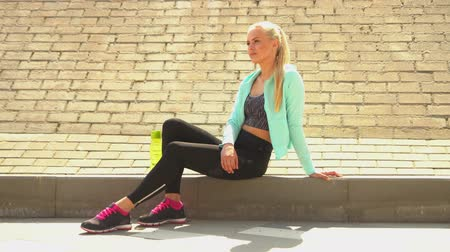 delgado : Young, attractive and sporty blond girl in sportswear relaxing outdoor. Healthcare, sport, fitness and lifestyle.
