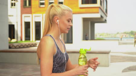delgado : Young, attractive and sporty blond girl in sportswear listening to the music and relaxing outdoor. Healthcare, sport, fitness and lifestyle.