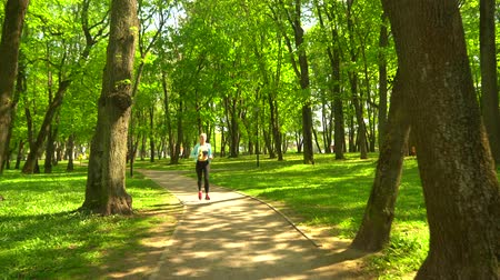 lélegzet : Young, attractive and sporty blond girl jogging outdoor in the park. Healthcare, sport, fitness and lifestyle. Stock mozgókép