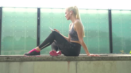 тощий : Young, attractive and sporty blond girl in sportswear listening to the music and relaxing outdoor. Healthcare, sport, fitness and lifestyle.