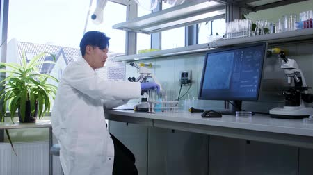 innovare : Scientist working in lab. Asian doctor making medical research. Laboratory tools: microscope, test tubes, equipment. Biotechnology, chemistry, science, experiments and healthcare concept.