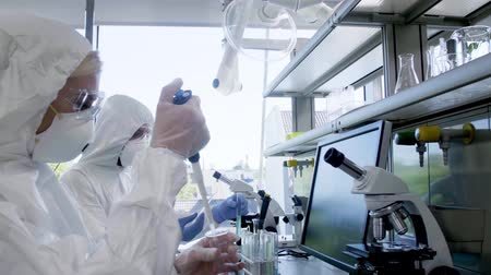 vaccino : Scientists in protection suits and masks working in research lab using laboratory equipment: microscopes, test tubes. Biological hazard, pharmaceutical discovery, bacteriology and virology.