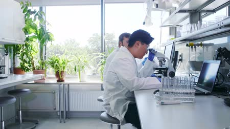 gyakornok : Scientist and his assistant working in lab. Doctor teaching intern to make analyzing research. Laboratory tools: microscope, test tubes, equipment.