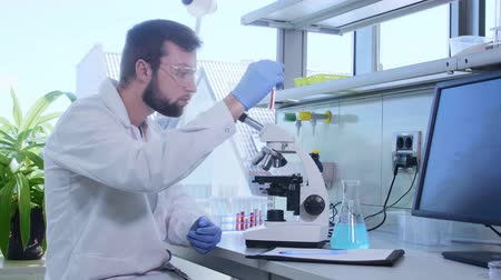vaccino : Scientist working in lab. Doctor making microbiology research. Biotechnology, chemistry, bacteriology, virology, dna and health care concept. Filmati Stock