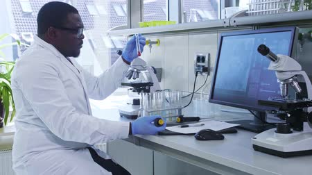 innovare : African-american scientist working in lab. Male doctor making microbiology research. Biotechnology, chemistry, bacteriology, virology, dna and health care.