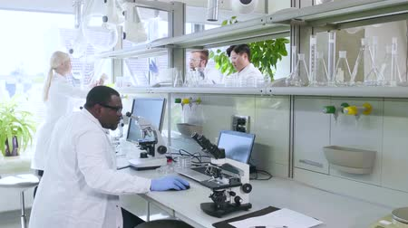 internar : Scientist and students working in lab. Doctor teaching interns to make analyzing research. Laboratory tools: microscope, test tubes, equipment. Biotechnology, chemistry, bacteriology, virology.