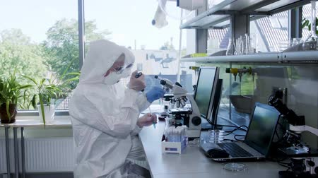 infectious : Scientists in protection suits and masks working in research lab using laboratory equipment: microscopes, test tubes. Biological hazard, pharmaceutical discovery, bacteriology and virology.