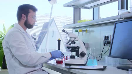 innovare : Scientist working in lab. Doctor making microbiology research. Biotechnology, chemistry, bacteriology, virology, dna and health care concept. Filmati Stock