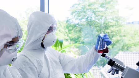 radioaktivní : Scientists in protection suits and masks working in research lab using laboratory equipment: microscopes, test tubes. Biological hazard, pharmaceutical discovery, bacteriology and virology.