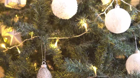 decorating : Beautiful Christmas tree decorated with balls and lights. Present boxes, gifts in front. Stock Footage