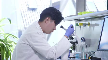 genetic research : Scientist working in lab. Asian doctor making medical research. Laboratory tools: microscope, test tubes, equipment. Biotechnology, chemistry, science, experiments and healthcare concept.