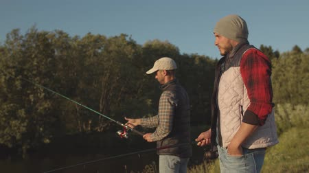 brochet : Fishermen friends with a spinning rod catching fish on a river. Fisher men on a weekend. Hobby, leisure and active summer and autumn concept.