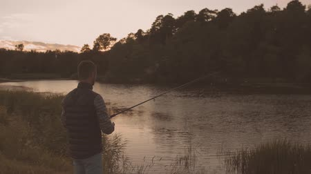 szczupak : Fisherman with a spinning rod catching fish on a river. Fisher man on a weekend. Hobby, leisure and active summer and autumn concept.