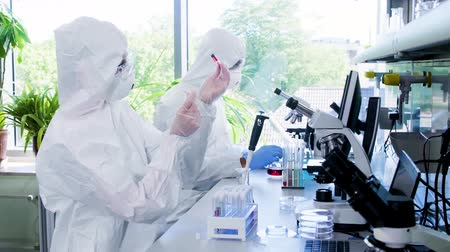 biological danger : Scientists in protection suits and masks working in research lab using laboratory equipment: microscopes, test tubes. Biological hazard, pharmaceutical discovery, bacteriology and virology.