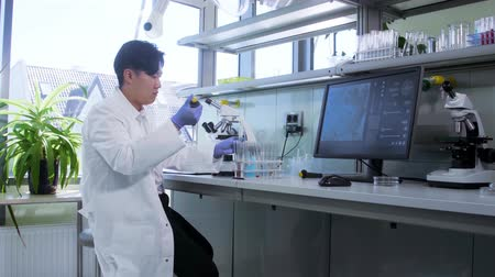 genetic research : Asian scientist working in lab. Doctor making microbiology research. Laboratory tools: microscope, test tubes, equipment. Biotechnology, chemistry, bacteriology, virology.