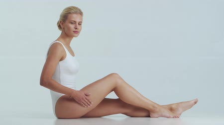 活性化させる : Young, beautiful, fit and natural blond woman in white swimsuit applying skincare cream. Massage, skin care, cellulite removal and weight loss.