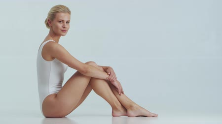 sports nutrition : Young, beautiful, fit and natural blond woman in white swimsuit applying skincare cream. Massage, skin care, cellulite removal and weight loss.