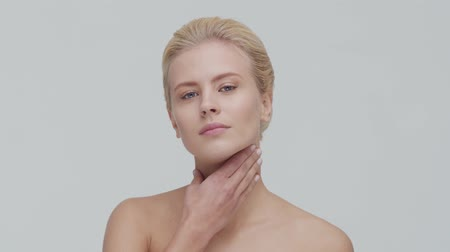 омоложение : Studio portrait of young, beautiful and natural blond woman applying skin care cream. Face lifting, cosmetics and make-up.