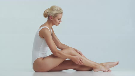masaj : Young, beautiful, fit and natural blond woman in white swimsuit applying skincare cream. Massage, skin care, cellulite removal and weight loss.