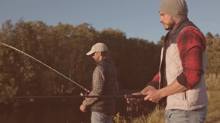 フィッシャー : Fishermen friends with a spinning rod catching fish on a river. Fisher men on a weekend. Hobby, leisure and active summer and autumn concept.